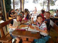 Děti sedící u oběda s pizzou